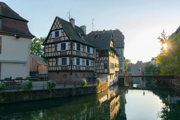 Old town and river channel in Strasbourg city Strasbourg, France - 26th August, 2019: View on the part of old town and river channel in Strasbourg city. Strasbourg is the capital and largest city of the Grand Est region of France and is the official seat of the European Parliament. grand est stock pictures, royalty-free photos & images