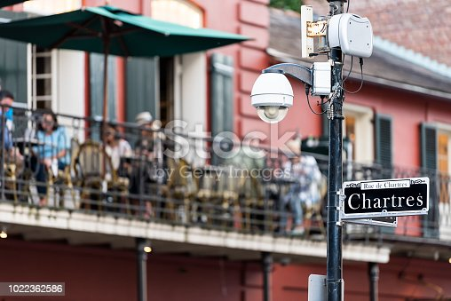 889246424istockphoto Old town Bourbon Chartres street in New Orleans, Louisiana town, city, cast iron balcony wall corner building, people sitting in restaurant outdoor bar during evening sunset, architecture 1022362586
