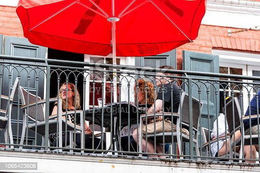 istock Old town Bourbon Decatur street in Louisiana town, city, cast iron balcony building, people sitting in restaurant outdoor cafe closeup 1065423608
