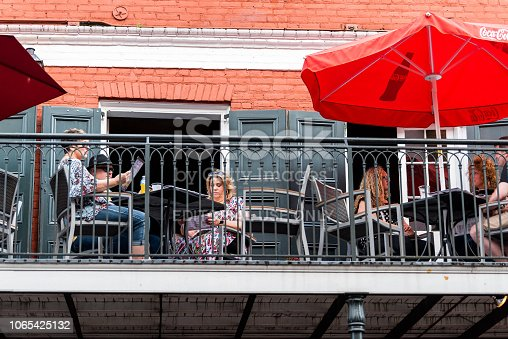 istock Old town Bourbon Decatur street in Louisiana town, city, cast iron balcony building, people sitting in restaurant outdoor cafe 1065425132