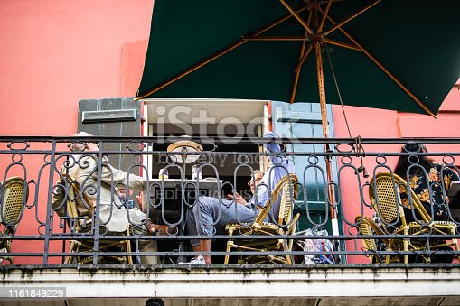 istock Old town Bourbon Decatur street in New Orleans, cast iron balcony, people sitting in outdoor restaurant 1161849229