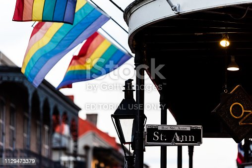 889246424istockphoto Old town Bourbon street in Louisiana town city with Saint Ann building party nightlife by restaurant outdoor bar in dark evening with lgbt flags 1129473379