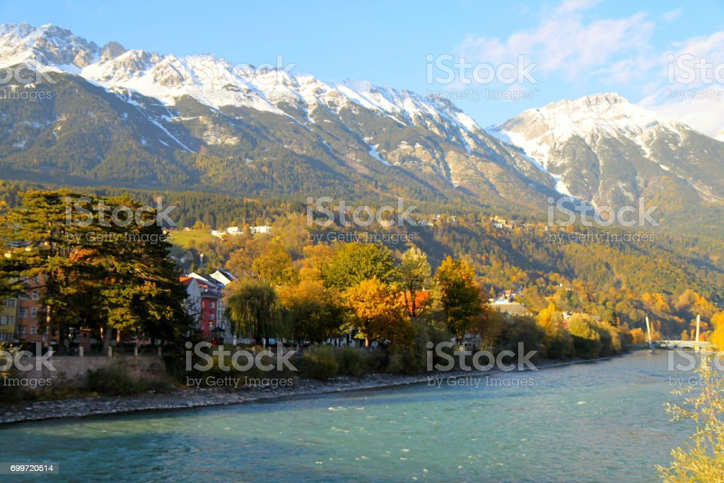 Old town buildings of Innsbruck, River Inn, gold colored autumn panorama and Idyllic North Tyrol snowcapped Karwendel mountain range at sunrise,  Austria stock photo