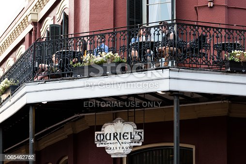 istock Old town Chartres street in Louisiana town, city, cast iron balcony building, people sitting in restaurant outdoor cafe Muriel's at Jackson Square 1065462752