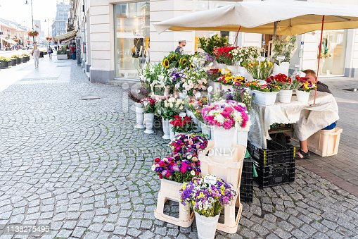Warsaw, Poland - August 23, 2018: Old town cobblestone street sidewalk during sunny summer day architecture with florist flower shop