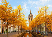 Street with canal and Old Church falling tower of Delft, Holland at fall