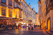 Tourists walking down an old town street in Prague in the evening.