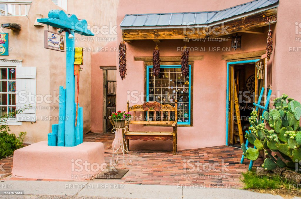 Old town plaza at hidden patio with San Pasquals shop and decorative sidewalk with brick paths, flowers, dried chiles, and gardens Albuquerque: Old town plaza at hidden patio with San Pasquals shop and decorative sidewalk with brick paths, flowers, dried chiles, and gardens Adobe - Material Stock Photo