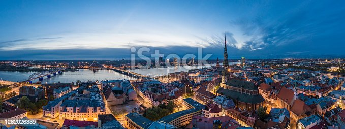 Historical buildings surrounding the St. Peters church in Old Town Riga after sunset