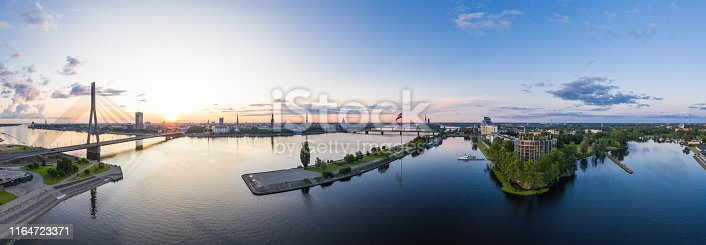 Panoramic view from Pardaugava towards Old Town Riga at sunrise. Zunda channel and AB dam and is in the foreground.