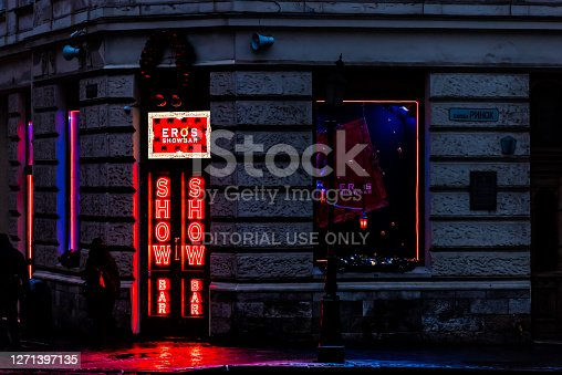 Lviv, Ukraine - December 28, 2019: Old town rynok market square in Lvov with red neon illumination at night for strip club Eros show bar and sign