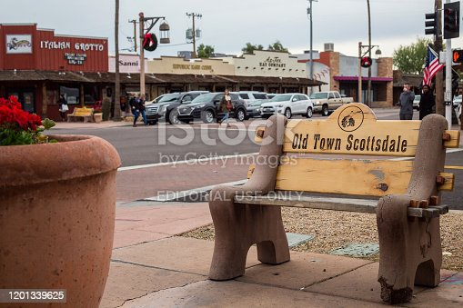 Scottsdale, USA - December 30, 2019. A bench advertising Old Town Scottsdale by a busy intersection in the outdoor tourism center just outside of Phoenix.