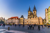 Prague, Czech Republic, May 13, 2019: people are walking down Old Town Square Stare Mesto in historical city centre. Gothic Church of Our Lady before Tyn, evening view, Bohemia