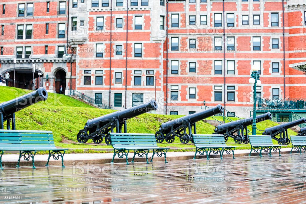 Old town street and view of hotel Chateau Frontenac with cannons and dufferin terrace in heavy rain stock photo