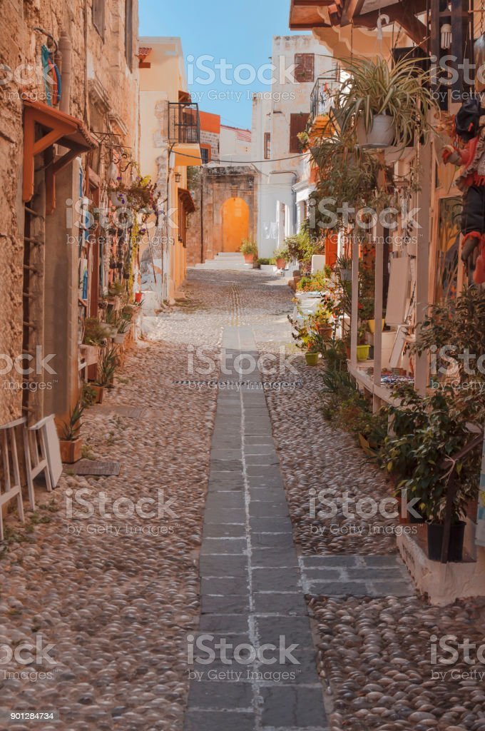 Old town street passage between building with flowers and grass in Rhodes town stock photo