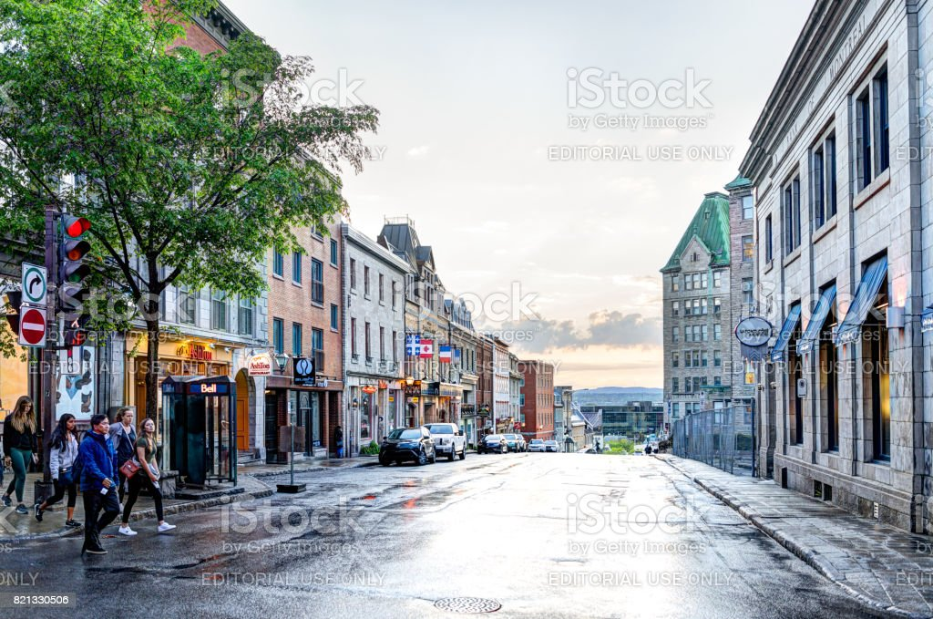 Old town street with people crossing Cote du Palais road and view of sunset stock photo