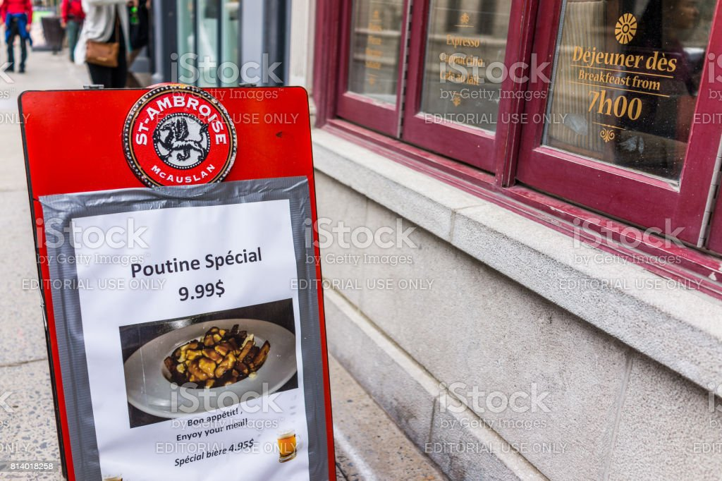 Old town street with sidewalk and poutine special sign by restaurant stock photo