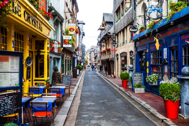 Old town streets - Honfleur, France Honfleur, Normandy, France - August 31, 2017: A few people walking in the cobblestoned streets of old town Honfleur. calvados stock pictures, royalty-free photos & images