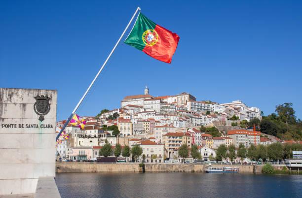 Altstadtansicht von Coimbra von Santa Clara Brücke mit Portugal Flagge Weben in den blauen Himmel – Foto
