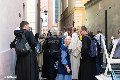 Warsaw, Poland - August 23, 2018: Old town with group of religious nuns and priests on historic street during sunny summer day together