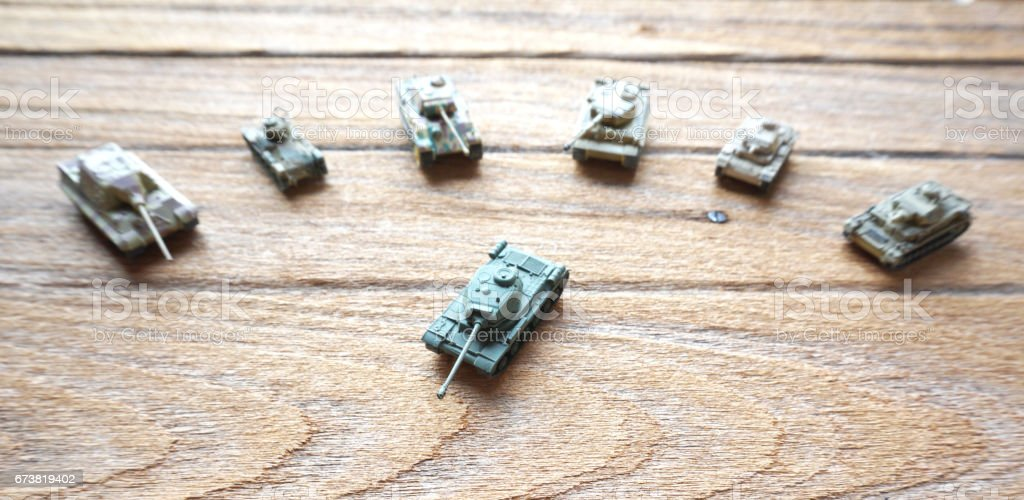 old toy tanks on wooden background. stock photo
