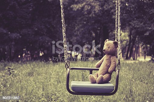 istock Old toy teddy bear sitting on swing in park 802311882