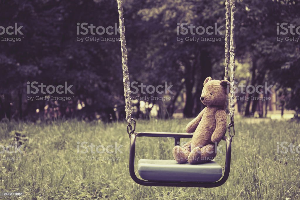 Old toy teddy bear sitting on swing in park stock photo