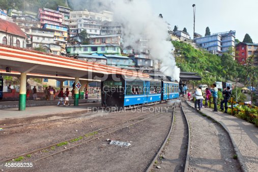 Darjeeling, West Bengal, India - May 18th, 2012: Steam engine of old Toy Train (N.F.795B)in the city of Darjeeling; people walking, photographing, working in the background, St. Columba's Church on the left.