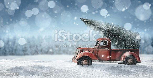 Old red toy truck with christmas tree loaded on the back