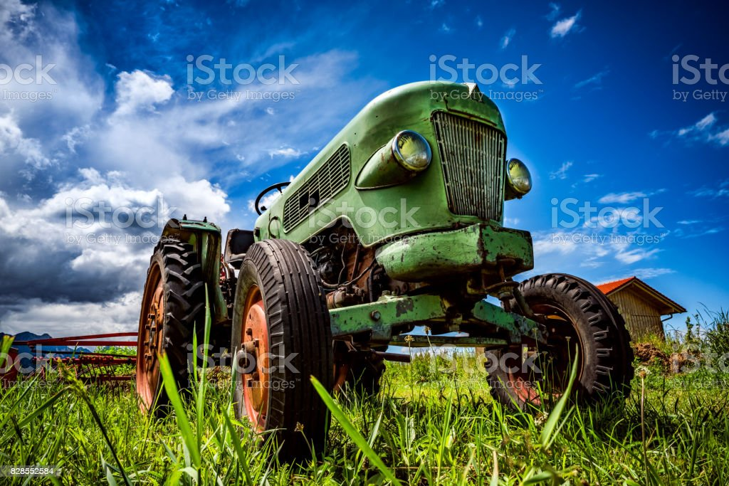 Old tractor in the Alpine meadows stock photo