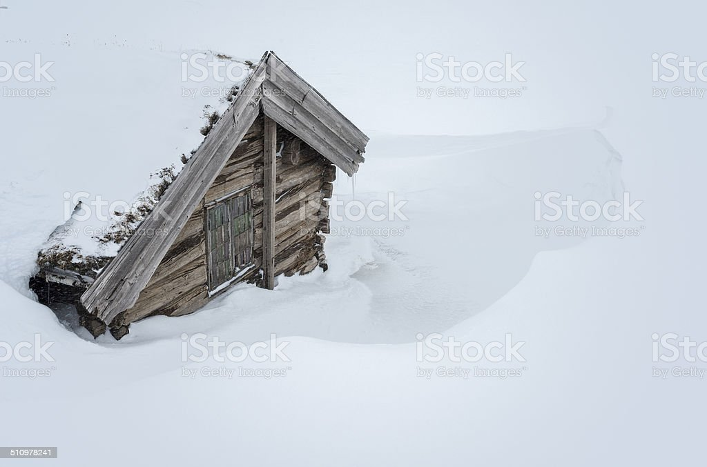 Old traditional Norwegian wooden log cabin house covered with snow stock photo
