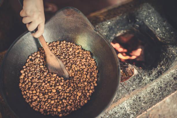 forma antigua tradicional de tostado de granos de café crudo en llamas - gato civeta fotografías e imágenes de stock