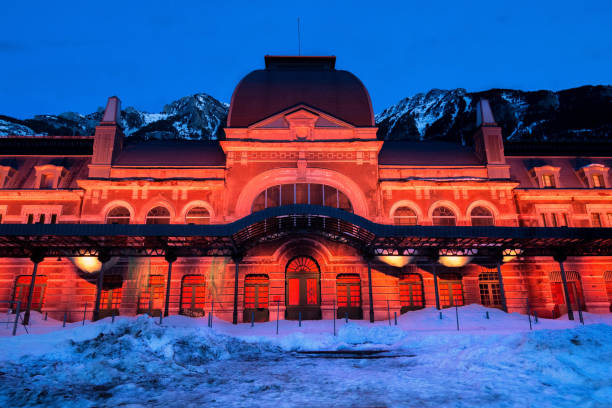 Old train station of Canfranc with the facade illuminated in reddish tones on a winter night with snow on the tracks,  Huesca, Spain stock photo