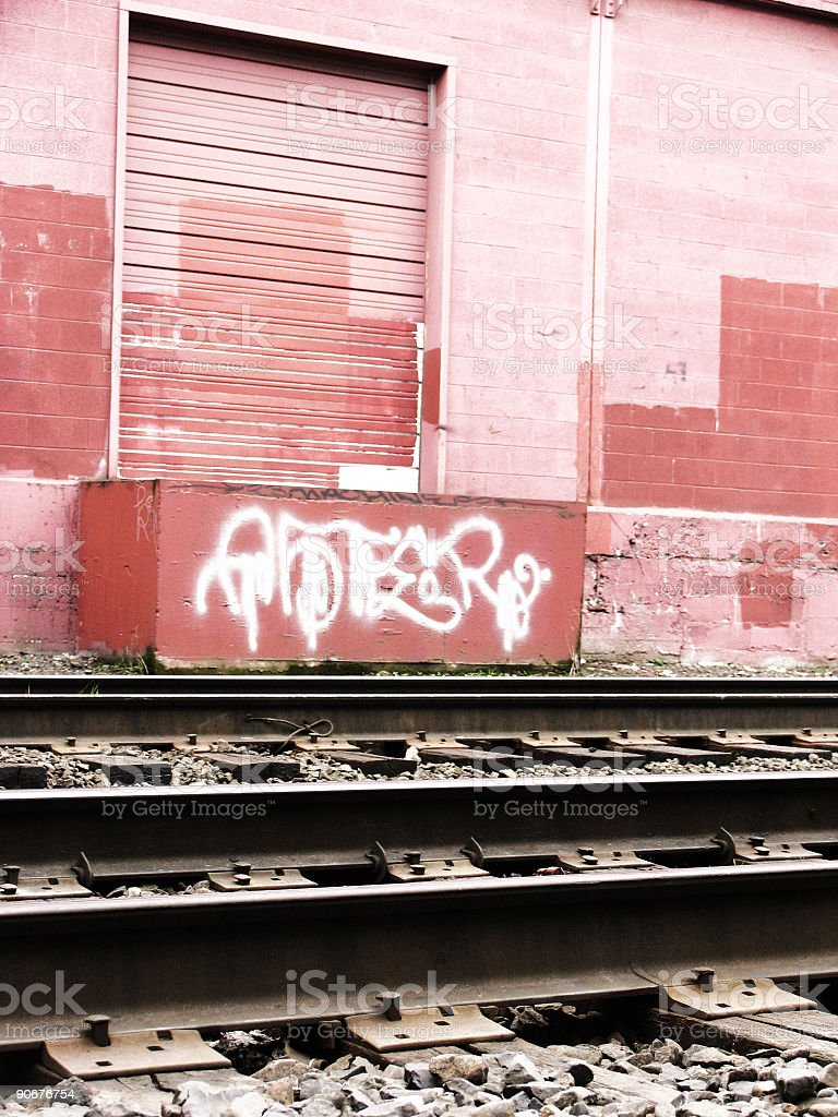 Old Train Tracks and Light Pink Wall with Door royalty-free stock photo