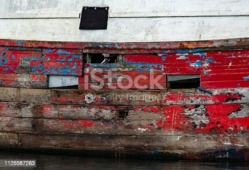 An old trawler, no longer in service, with holes and decaying wood