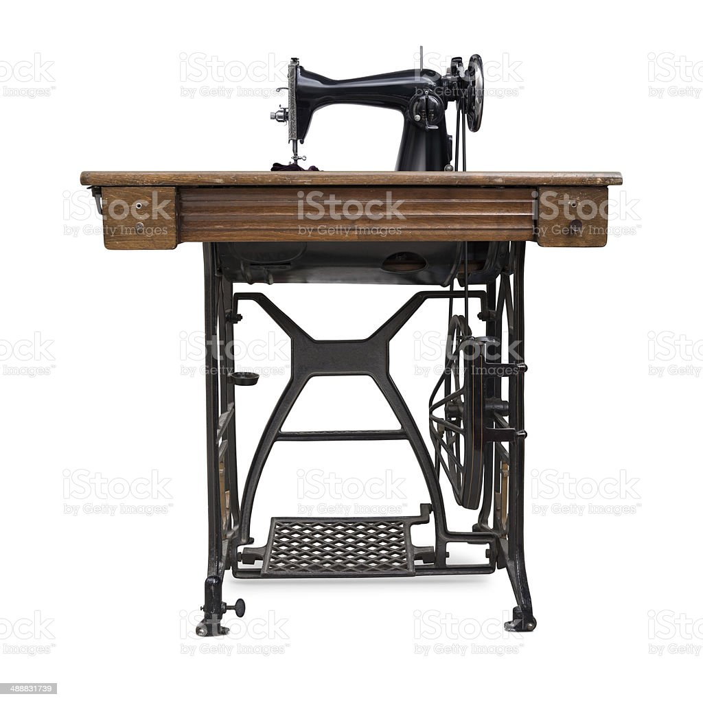 Old Treadle Sewing Machine Old treadle sewing machine, isolated on white background. Antique Stock Photo