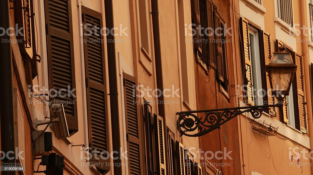 Old treet electric lamp on old town building and shutters stock photo