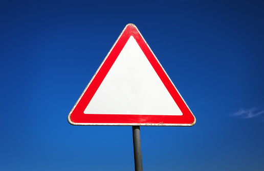 istock Old triangle traffic sign on the blue sky background 613527642