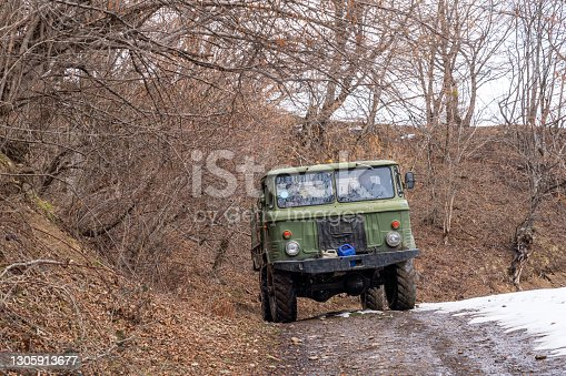 istock Old truck on a dirt mountain road 1305913677