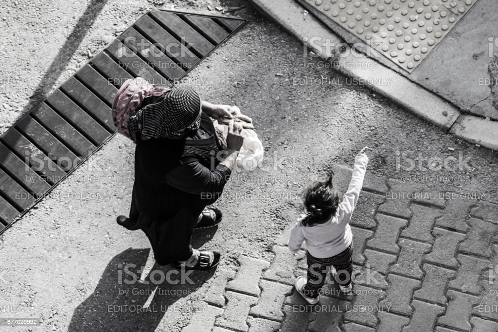 Old turkish woman on the street with a child stock photo