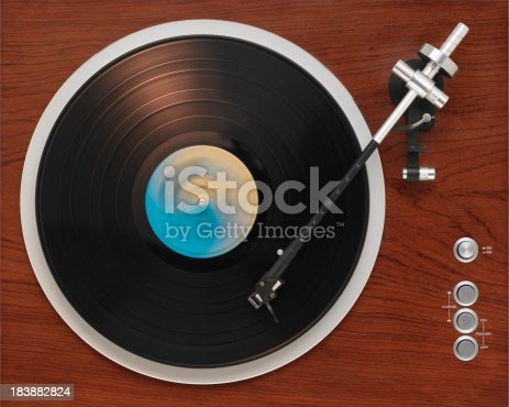 An old turntable from the '70s playing a record album. Direct overhead view.