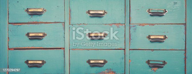 Old turquoise and brown colored wooden file and document cabinet with drawers background