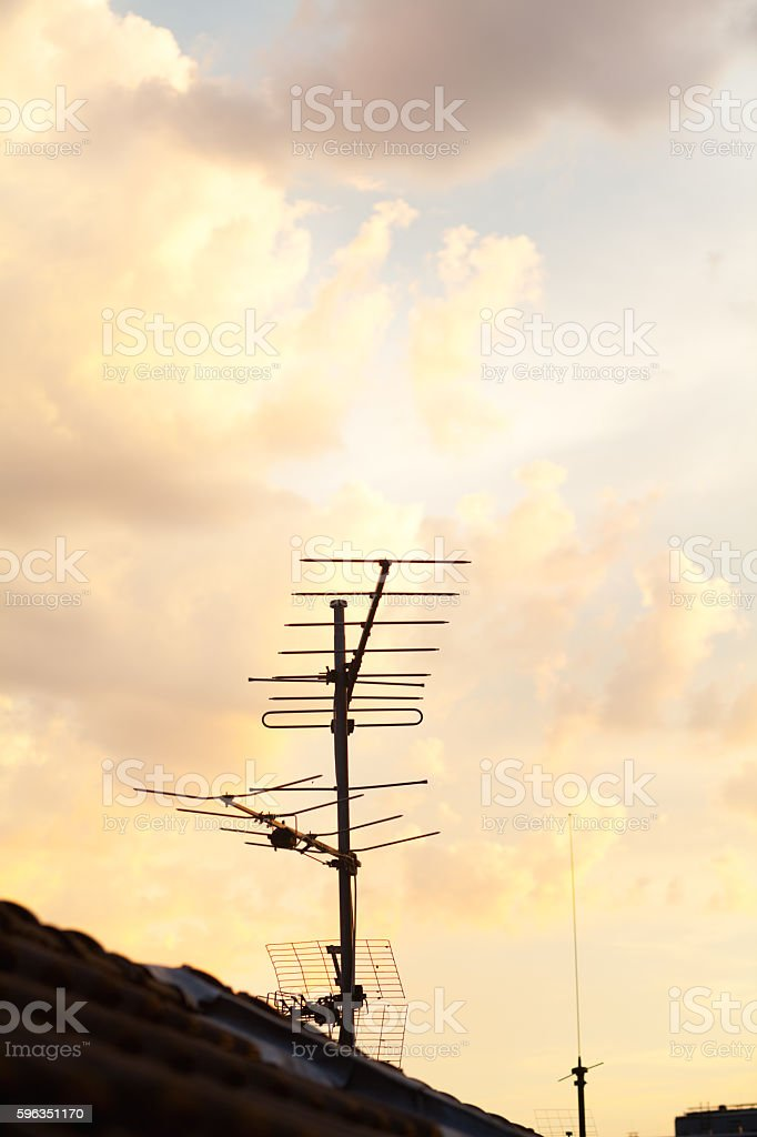 Old tv ntenna on roof and sunset sky royalty-free stock photo