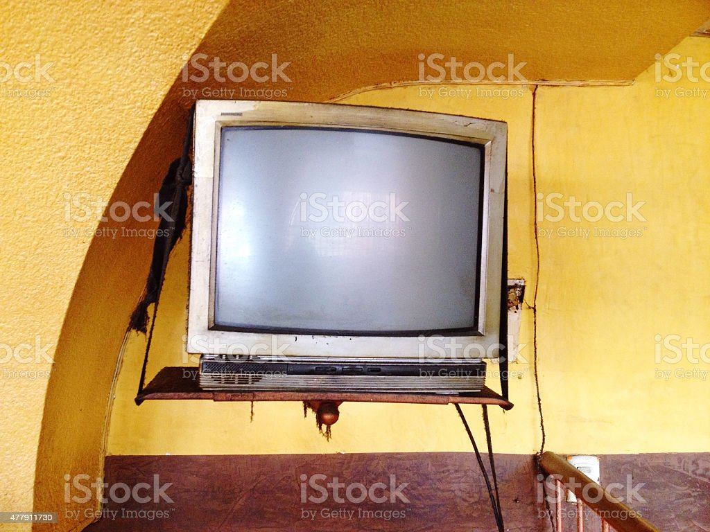 A old, dirty TV mounted on a wall.
