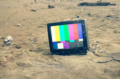 old TV playing color bars in desert