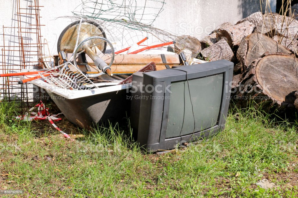 Old TV set and the rest of bulky trash. Old TV thrown away next to a...
