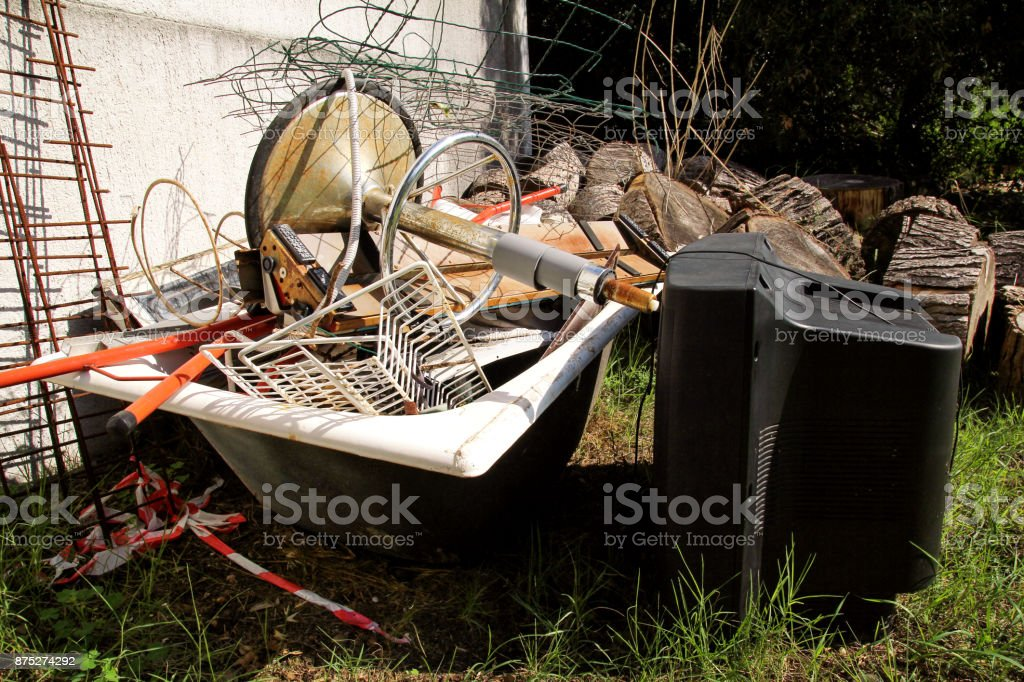 Old TV set and the rest of bulky trash. Old TV thrown away next to a wall with a pile of mixed garbage. in natural environment. Recycling industry. Not Ecology. Ecology. Recycled material and wastes. stock photo