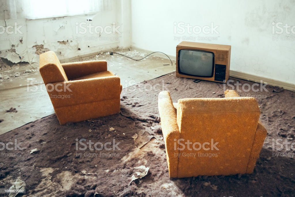 Old TV set on the floor and two vintage armchairs on damaged carpet...