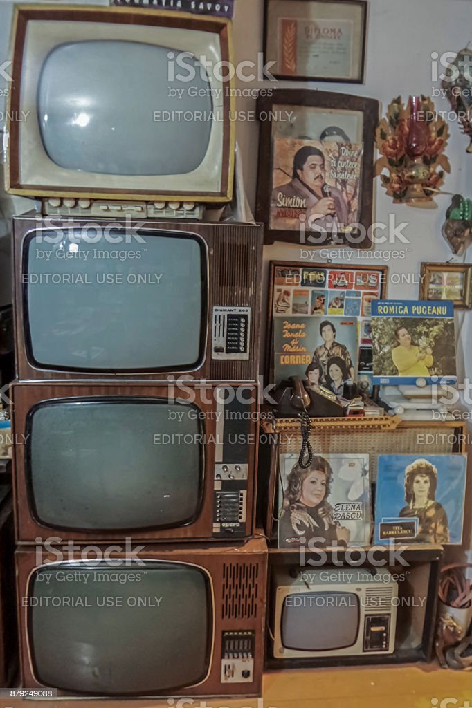 Old TVs and vinyl music discs, collected in a room.