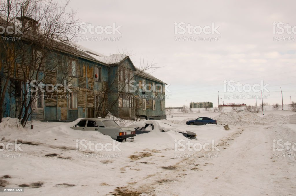Old two-storied  blue house in winter with snow outdoor. Poverty and misery, North stock photo